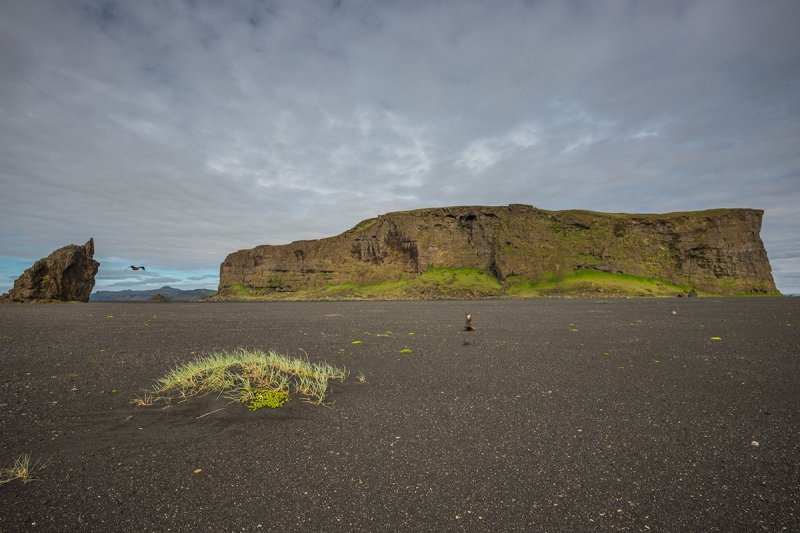 Hjörleifshöfði is a huge rock or an island on dry land, standing approximately 220 meters high above the black sand by the coastline at Mýrdalssandur in the South Region in Iceland.