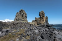 The two large pillars towering over their surroundings at the shore near Hellnar in Snæfellsnes are Lóndrangar.